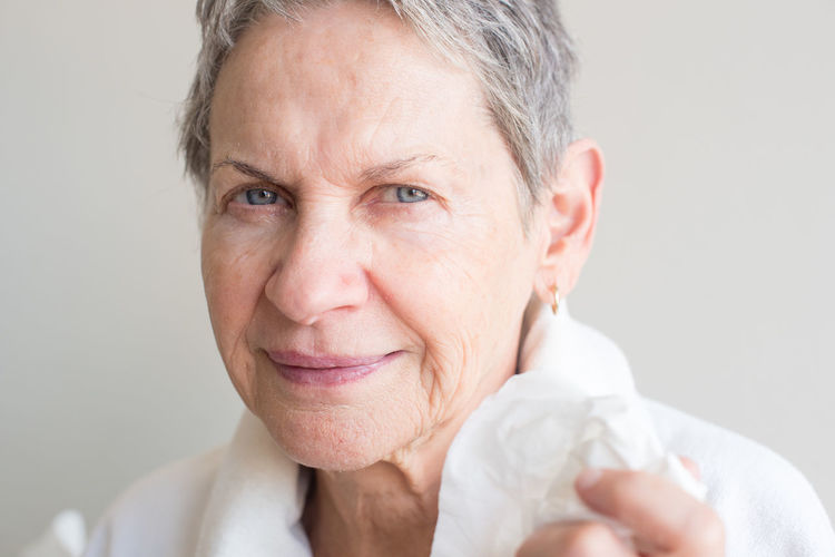 Portrait of sick older woman with tissue Adult Adults Only Close-up Day Front View Gray Background Gray Hair Headshot Indoors  Leisure Activity Looking At Camera Mature Adult One Person People Portrait Real People Senior Adult Senior Women Smiling Studio Shot White Background