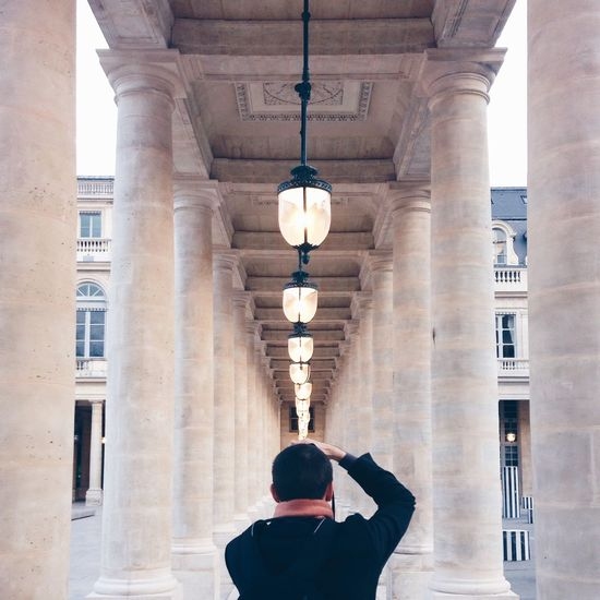 Man Standing In Corridor Along Pillars