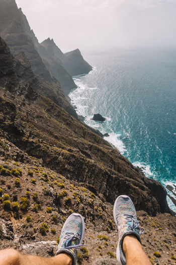 Low section of man standing on cliff by sea