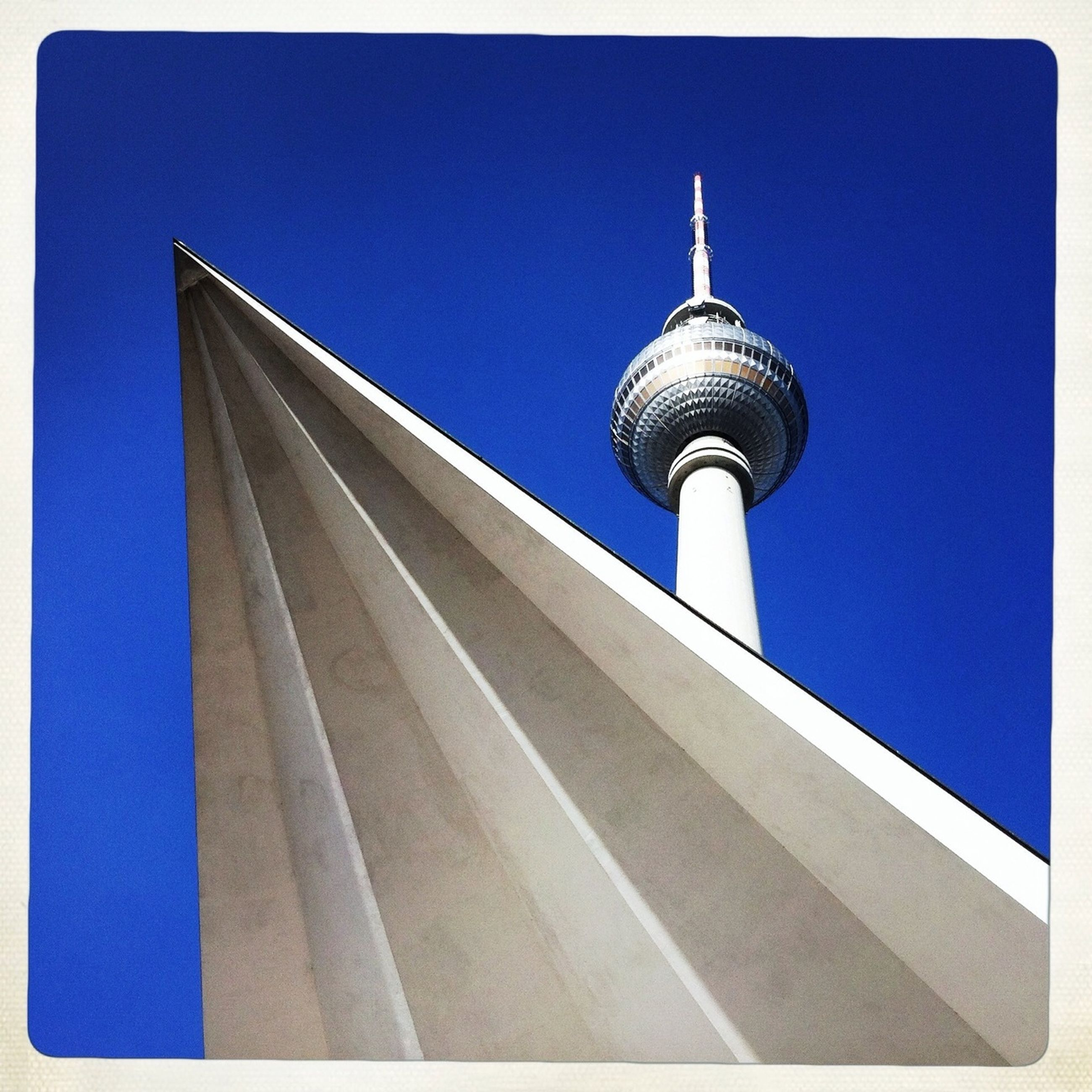 architecture, built structure, tower, communications tower, tall - high, famous place, building exterior, international landmark, blue, travel destinations, spire, tourism, low angle view, clear sky, capital cities, travel, fernsehturm, television tower, culture, communication
