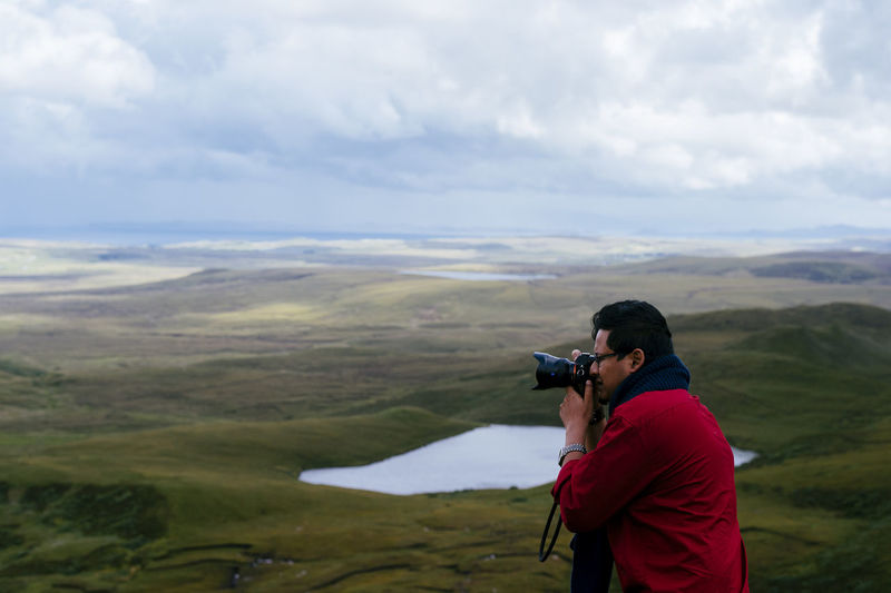 Side view of male photographer photographing at isle of skye