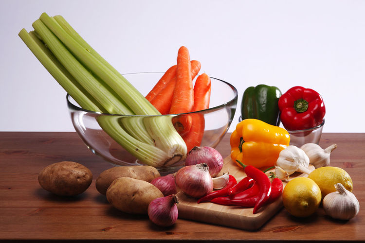 Various fruits and vegetables on plate against white background