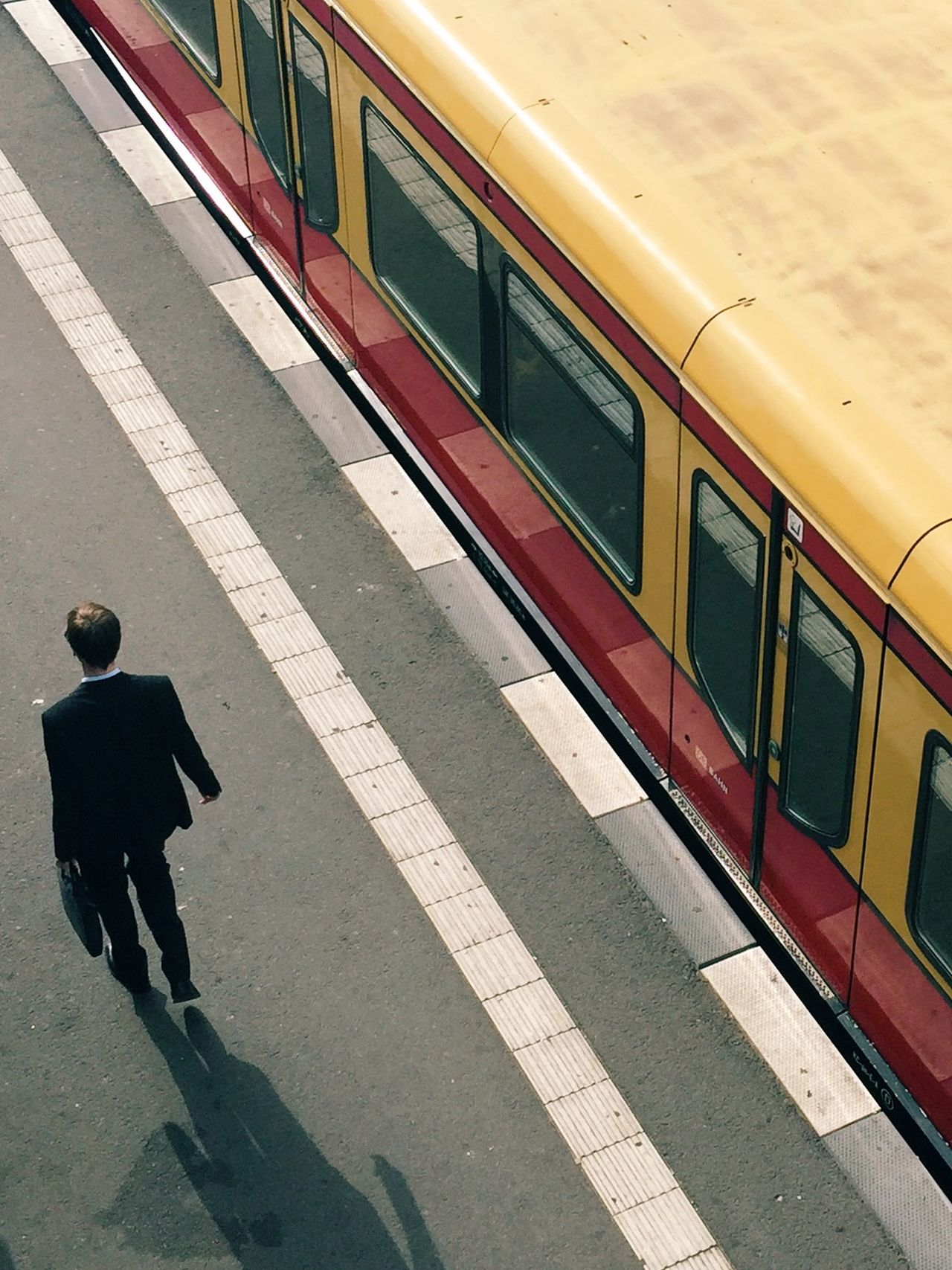 High Angle View Of Man Walking On Railroad Station