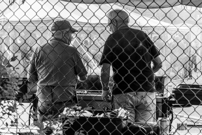 Two Senior Men Grilling Bratwurst Cooking Grilling Adult Behind Black And White Bonding Brats Chainlink Fence Day Festival Friendship Grill Meats Men Monochrome Nature Outdoors People Real People Rear View Standing Street Teamwork Togetherness Two People