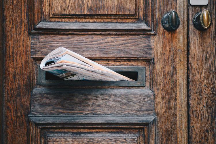 Close-up of newspaper in door