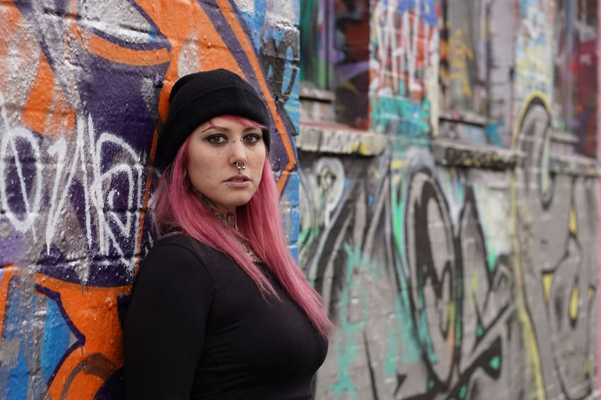 Alternative Authentic Casual Clothing Emo Girl Graffiti Inked Lifestyles Looking At Camera Person Pierced Piercing Pink Hair Portrait Punk Real People Street Tattoo Tattooed Urban Wall Woman Young Adult Young Women Youth