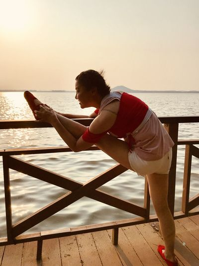 Ballerina dancing on pier by lake at sunset