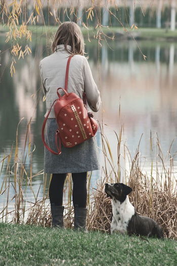 Animal Themes Casual Clothing Childhood Day Dog Domestic Animals Full Length Grass Lake Leisure Activity Lifestyles Mammal Nature One Animal One Person Outdoors People Pets Real People Rear View Sitting Standing Water
