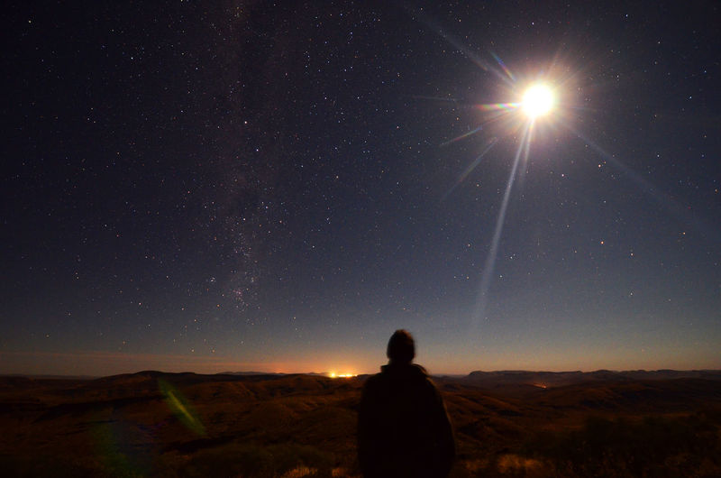 Rear view of man against moonlight in sky at night