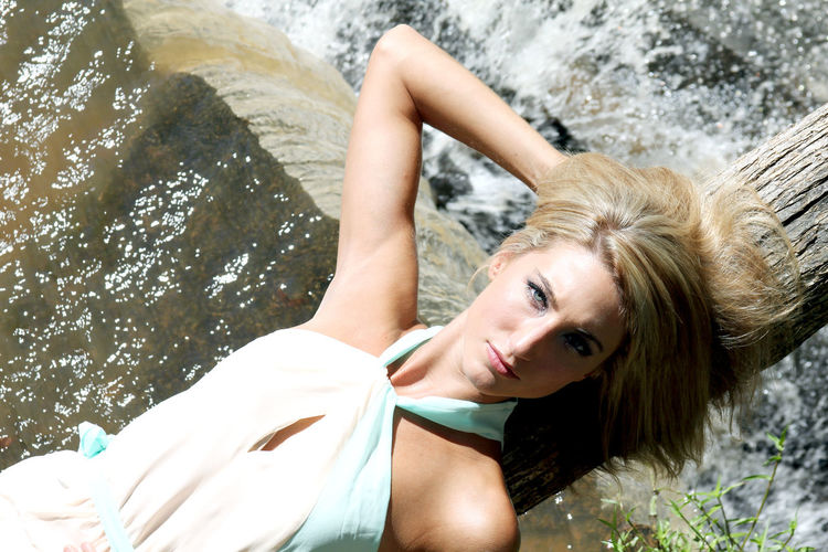 High angle portrait of woman lying on waterfall