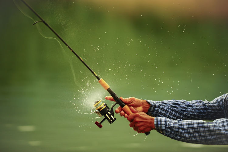 Man holding fishing rod by water