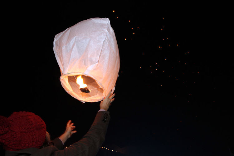 Rear view of woman leaving illuminated paper lantern against sky at night