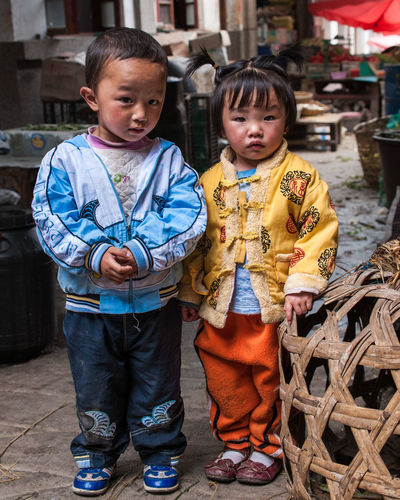 "Today in Chinese microfashion - A couple of adorable Chinese siblings at the border between Yunnan and Tibet. I love how the boy is dressed in ""western fashion"" while the girl prefers traditional Chinese clothing. Fashion Traditional Clothing Travel Photography Adorable Bonding Boy & Girl Boy And Girl Brother & Sister China Cute Elementary Age Full Length Lifestyles Looking At Camera Microfashion Portrait Real People Sibling Standing Tibet Togetherness Travel Portraits Travelphotography Village Life Yunnan"