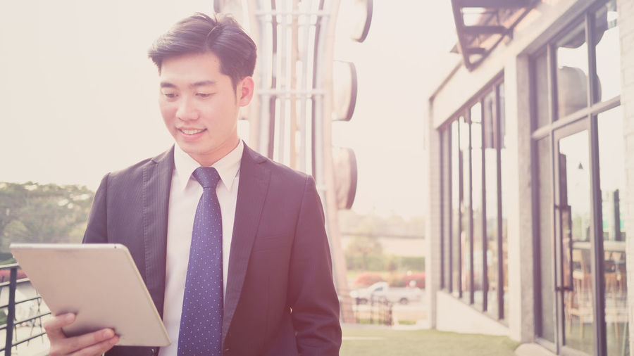 Smiling young businessman using digital tablet