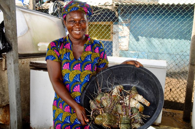 Portrait of smiling woman holding lobsters in container