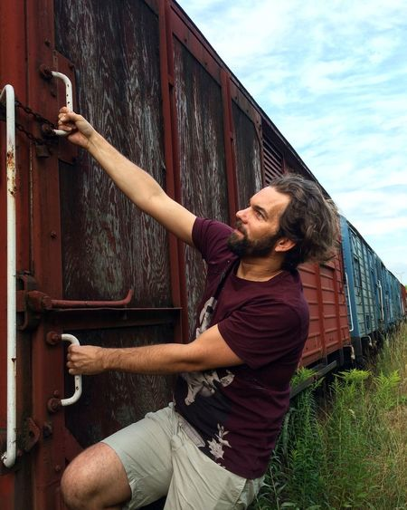 Bearded man hanging on train