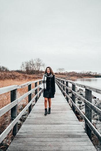Portrait of woman walking on footbridge against sky