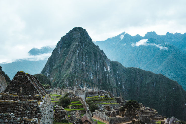 Old ruins of machu picchu against mountains during foggy weather