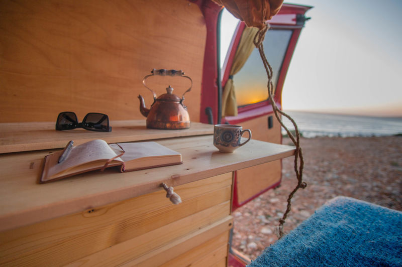 Book And Cup In Motor Home At Beach