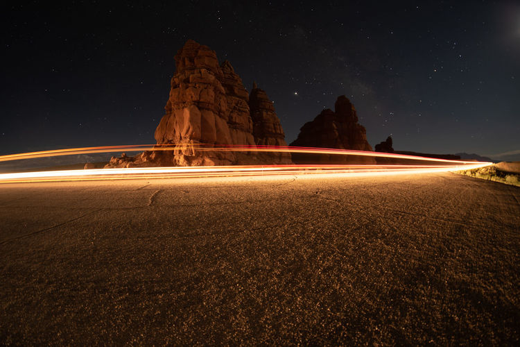 Light trails on rock formation against sky at night