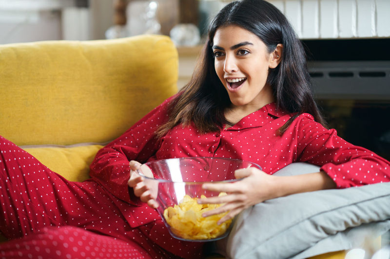 Portrait of smiling young woman in watching television sitting on sofa