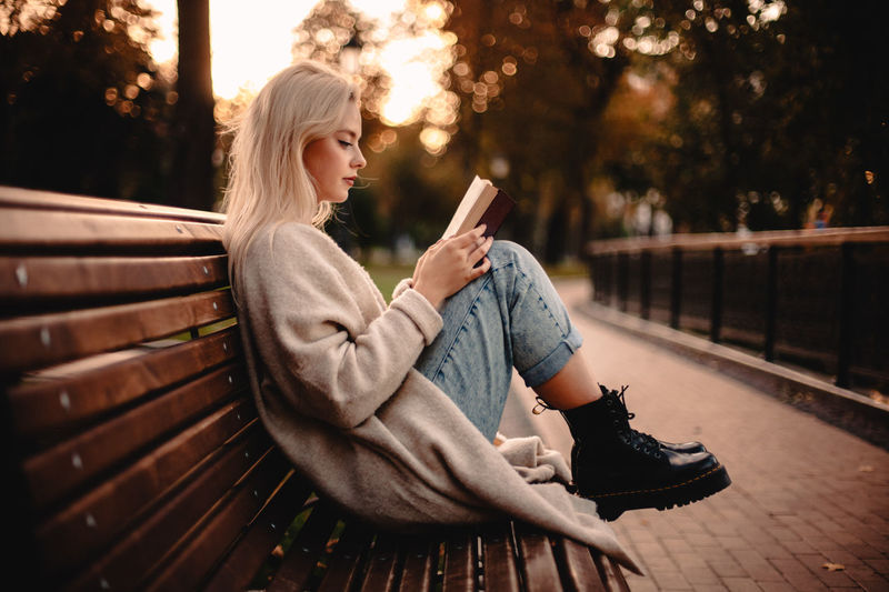 Young woman using phone while sitting on bench