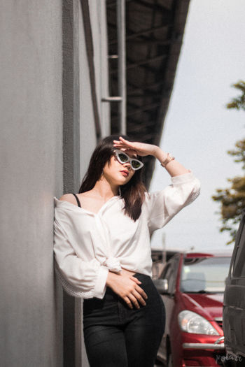 Young woman wearing sunglasses standing against car