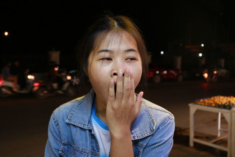 Young woman yawning at night