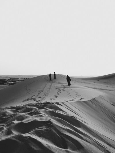 High Angle View Of Women Wearing Hijab Walking In Desert