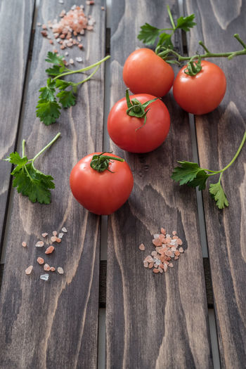 High angle view of fresh tomatoes and cilantro on table