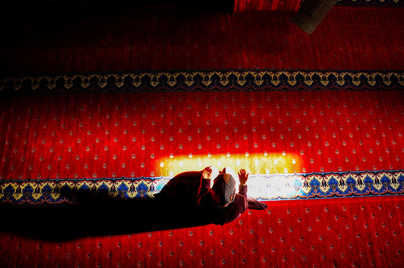 Directly above shot of sunlight falling on woman praying in mosque