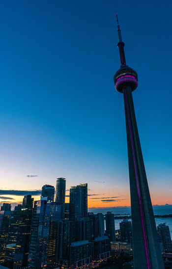 Low angle view of cn tower against clear blue sky during sunrise
