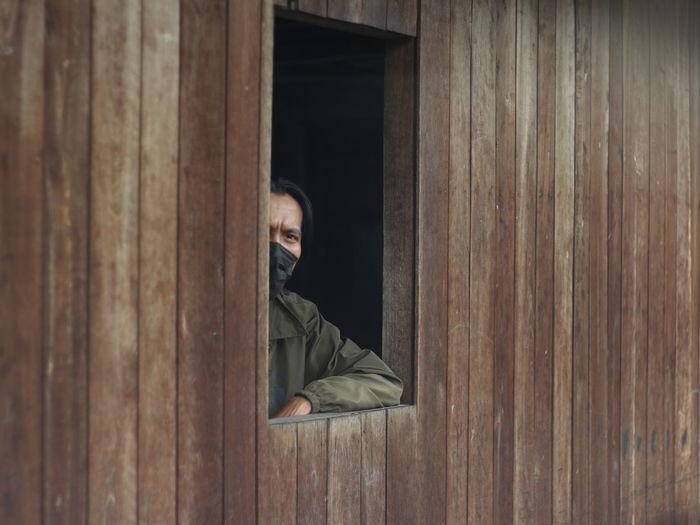 Portrait of man sitting on wooden windows
