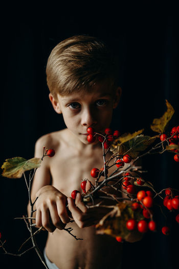 Portrait Of Boy Holding Berries Against Black Background