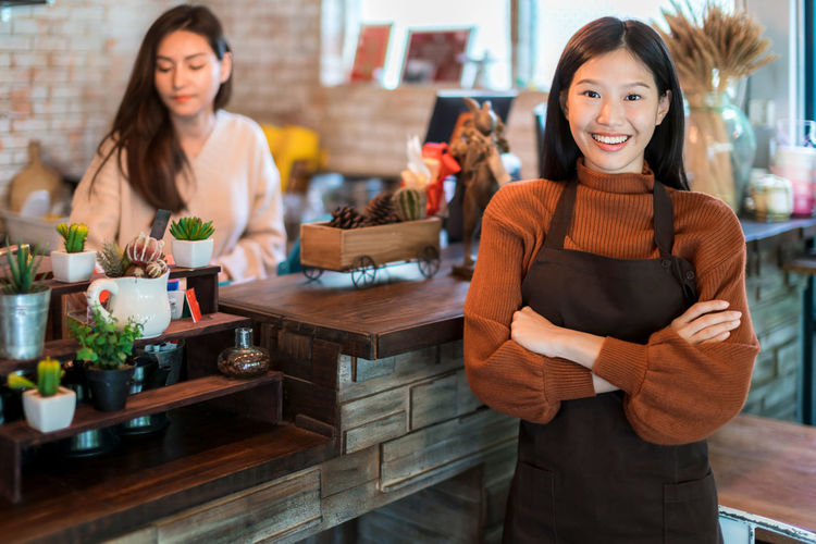 Portrait of smiling barista with arms crossed standing in cafe
