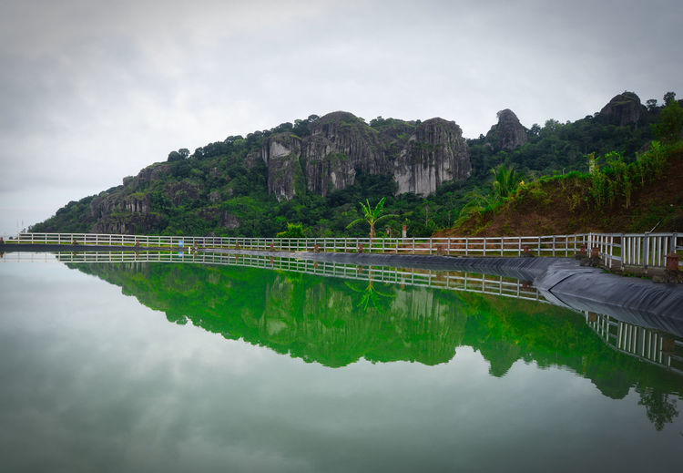 When morning at Embung Nglanggeran, Gunung Kidul, Yogyakarta, Indonesia. Water Reflection Sky Nature Mountain Scenics - Nature Beauty In Nature Tranquility Waterfront Lake Tranquil Scene Tree Plant Architecture Day No People Non-urban Scene Built Structure Standing Water Outdoors EyeEmNewHere EyeEm Best Shots EyeEm Nature Lover EyeEm Selects Beauty In Nature