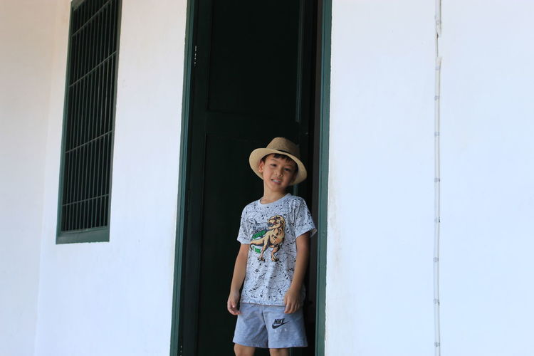 Portrait of boy standing at doorway