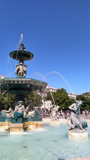 View of fountain at beach against blue sky