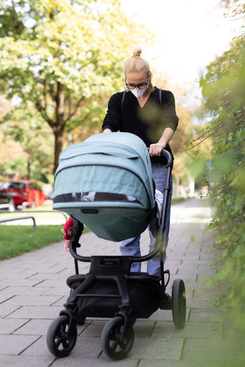 Full length of woman wearing mask with stroller at park