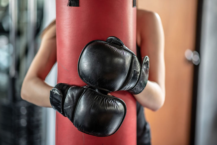 Midsection Of Woman Embracing Punching Bag In Gym