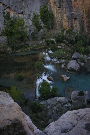 Scenic view of river stream amidst rocks
