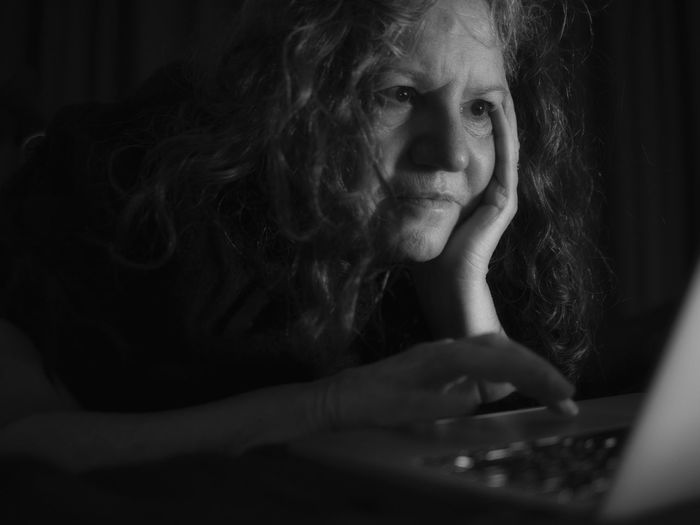 Close-Up Of Thoughtful Senior Woman Using Laptop In Darkroom
