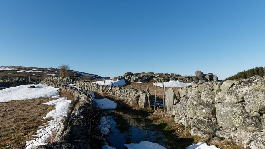 Path Path In Nature Nature Nature_collection Nature Photography Winter Cold Temperature Cold Stone Stone Wall Rock Rock - Object Blue Sky Hiking Field Fieldscape Lozère  Aubrac Mountain Freedom Lonely Loneliness Snow Sky Scenics - Nature Clear Sky Beauty In Nature Tranquility Tranquil Scene Day No People Outdoors Water Copy Space Blue Architecture Solid Built Structure River Non-urban Scene Arch Bridge