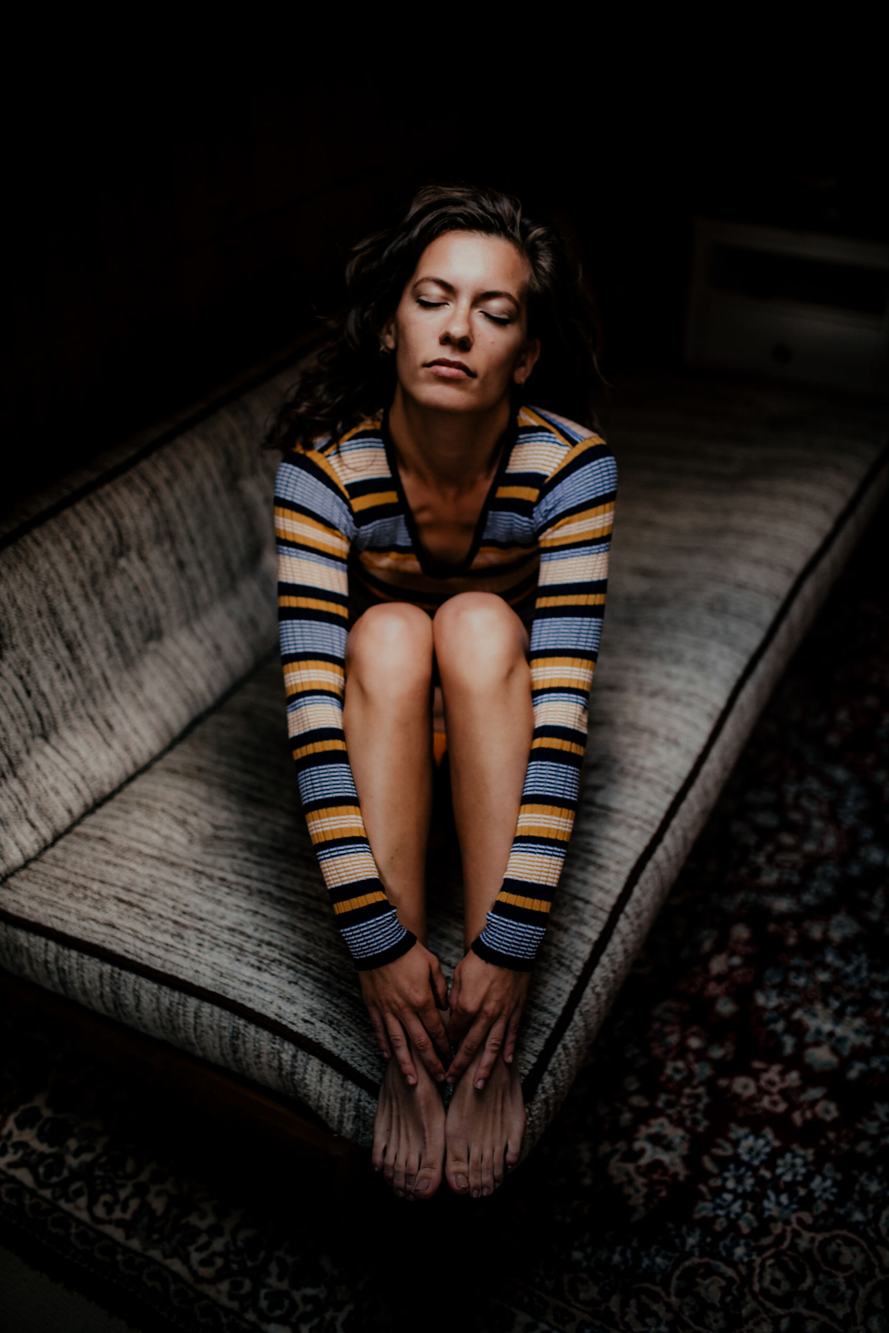 one person, sitting, indoors, front view, full length, women, young adult, real people, lifestyles, young women, adult, casual clothing, leisure activity, beautiful woman, beauty, clothing, looking, hairstyle, depression - sadness, contemplation