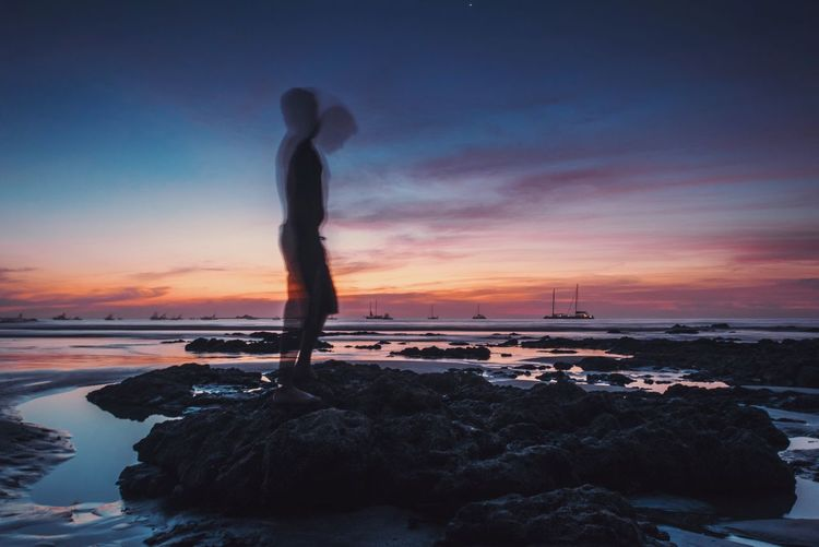 Blur image of silhouette man standing on rock at sea shore against sky during sunset