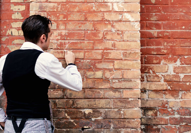 Rear view of man standing against brick wall