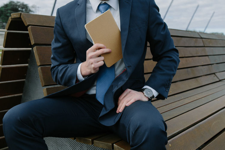 Midsection of businessman putting book in blazer