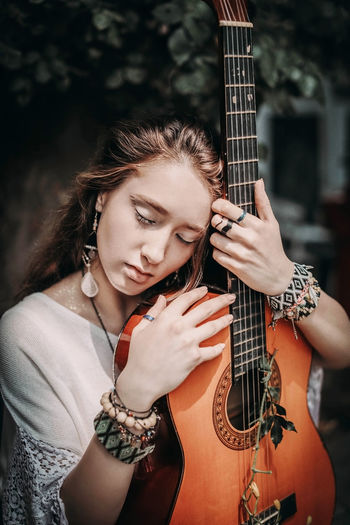 Young hippie brunette woman in white boho blouse hugging the guitar