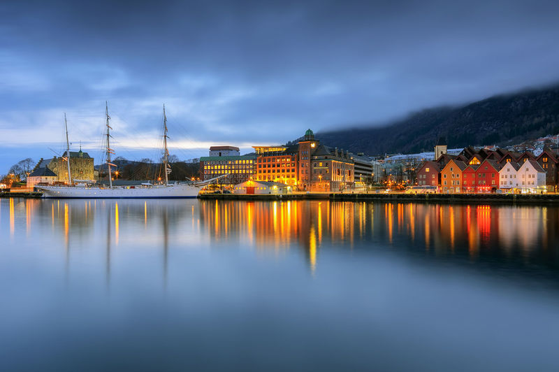 Illuminated Buildings Reflecting On Calm River Against Cloudy Sky