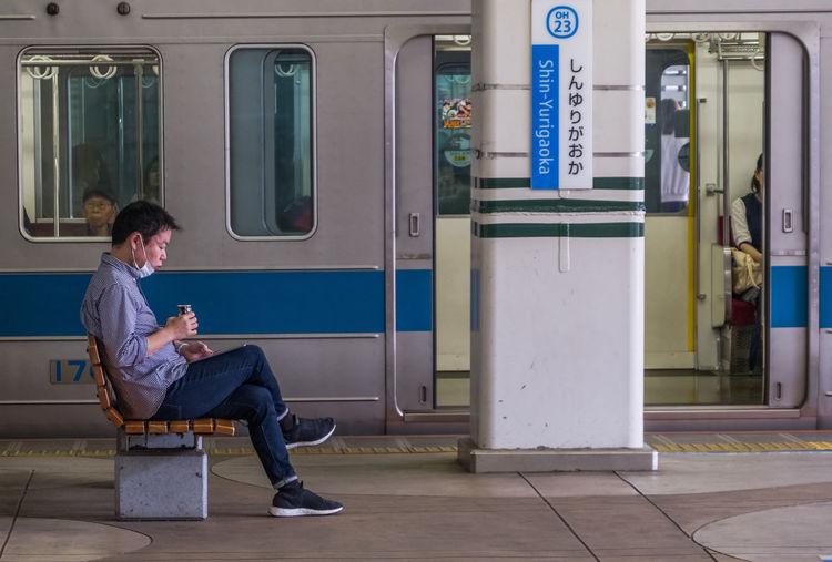 Full length of man sitting on seat